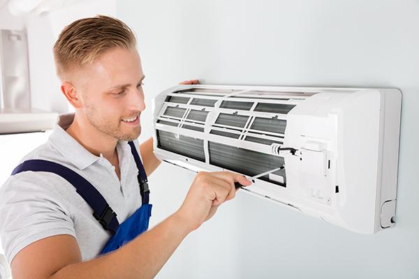 mężczyzna w stroju roboczym, z śrubokrętem montujący klimatyzator