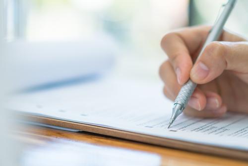 ręka z długopisem wypełniająca formularz